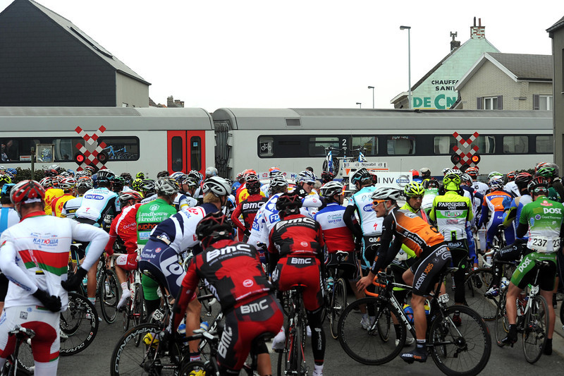 A closed railway-crossing halts the race after one hour - but the peloton has still managed over 50-kilometres in that first hour..!
