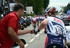 Andre Greipel is tinkering with his team radio -  a Lotto mechanic comes to his aid...