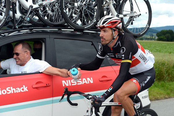 Fabian Cancellara collects bottles as the pace in the main peloton settles down...