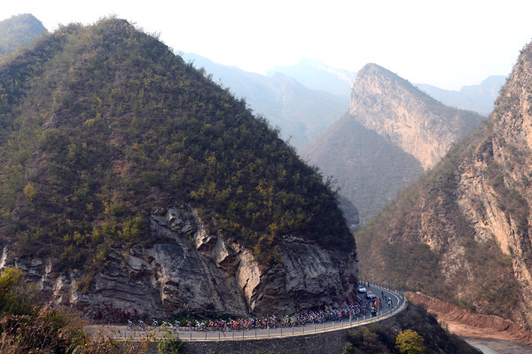 The peloton climbs through the Western Hills region of mountains...