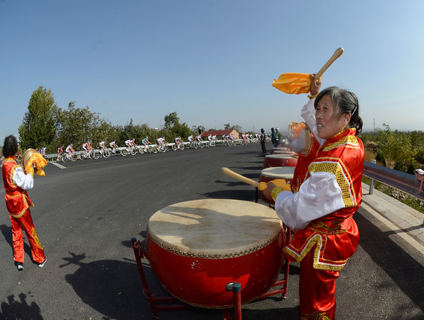 A group of Chinese drummers encourages the peloton as it speeds by...