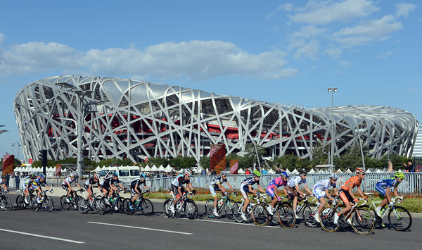 The peloton accelerates away from the Birds Nest Stadium with blue, cloudless skies keeping the air clean today...