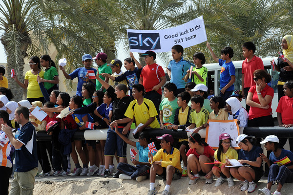 There's a big group of school children cheering at the Tour of Qatar cyclists...