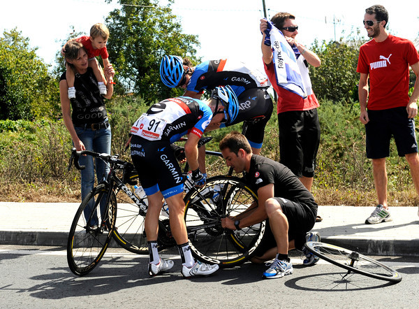 Andrew Talansky makes a wheel change while Johan Van Summeren quietly waits to pace him back...