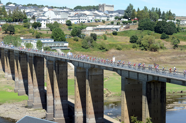 The peloton is at full stretch as it crosses the famous bridge over the Rio Loio...