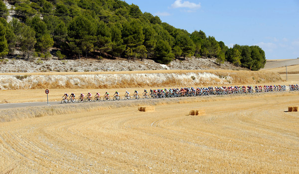 The peloton is also experiencing dry and hot conditions as it maintains a steady pace in pursuit...