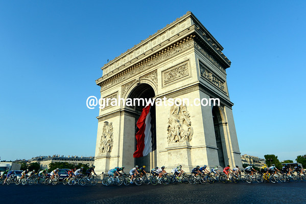 The sun is setting on the Arc de Triomphe as the Tour de France makes a first-ever passage around the famous monument...