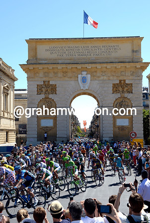 The Tour slips through the arch in Montpellier on its way to the official start...