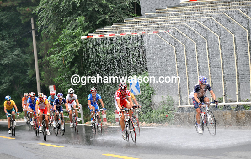THE CYCLISTS PASS BENEATH A WATER SPRAY AT THE 2008 OLYMPIC GAMES