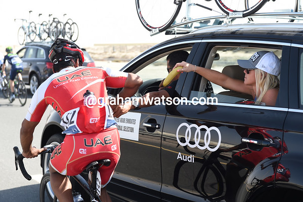Nasar El Mamari is spoilt for choice as he gets water and a banana from the team car...