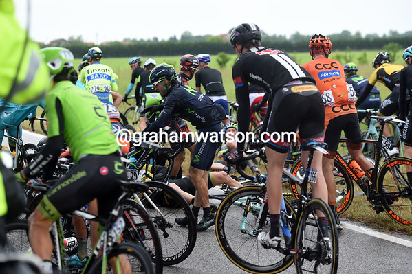 The road is blocked as riders are either stopped, or trying to get away on the wet grass...