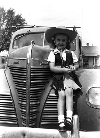 Adorable little girl in her cowgirl outfit on an old Plymouth