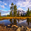 Mt. Rainier with swirly clouds is beautifully reflected in a small seasonal tarn.
