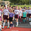 The varsity girls soccer team entered the field for their Friday game with aspiring youth players and the football team cheering.
