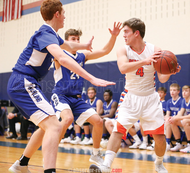 Kyle Berna looks to pass the ball under pressure from two Haverling defenders.