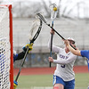 Hannah Keech takes an illegal cross-check to the face as she shoots in the game Saturday, April 28.