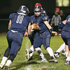 Zach Elliott (11) grabs the ball from quarterback Derrick Lewis (14) in the Saturday night game against Lansing.