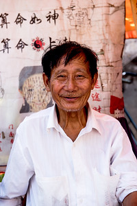 A local man sells Chinese face reading cards and medicinal goods at a farmer's market in Guilin, China