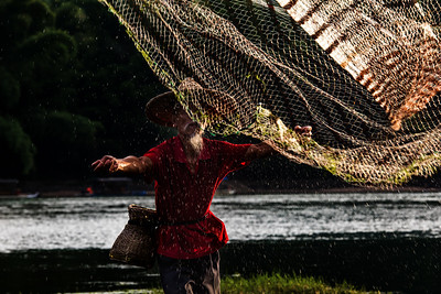 A cormorant fisherman demonstrates the art of casting a net into the Lijian River near Yangshuo in the Guilin region of China. This tradition of using birds to dive into the water to catch fish dates back to the first millenium. Today,  this ancient technique is practiced mainly to support tourism in the area.