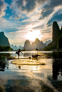Netcasting in silhouette, Li River, China