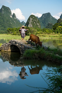 Farmer crossing an ancient stone bridge with Karst mountains in the background