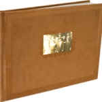"""11x8.5 Nubuck Photo Books (Premium Covers & Bindings) - Designed by Jodi  Make your book into a striking presentation with luxurious light brown nubuck leather. Customize a two-line title and choose a picture for the ornately framed, debossed 2.5 x 4"""" cover photo. Edges feature debossed detailing and heavyweight, archival quality paper is hinge bound so pages lay flat.    Cover:Nubuck Colors:Tan Binding:Hinge Base price:$1,047 for 20 pages Slip Case (optional):  $200 Add'l pages:$8 per page Max pages:250"""
