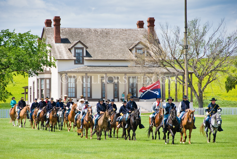 "Re-enactors at Ft. Abraham Lincoln State Park cross the parade grounds in front of the reconstructed home of Lt. Col. George Armstrong Custer. Image from the book ""Crossing the Plains with Custer"", also appeared in April 2018 issue of TrueWest magazine."