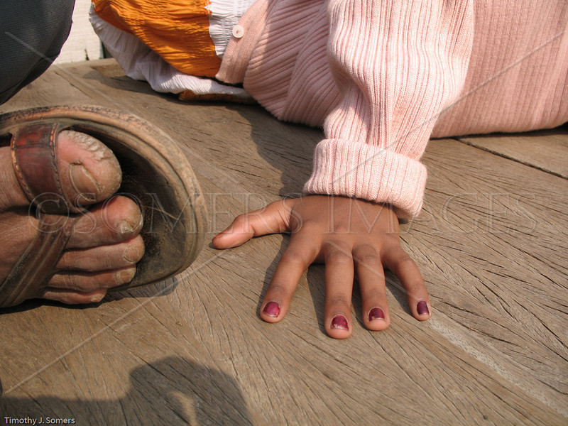 Man's foot, girl's hand, India