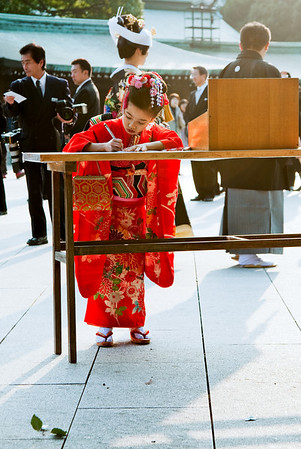 Shichi Go San Matsuri:  A girl wears a kimono at the temple marking her achieving the age of 7.  She is writing a wish on a slip of paper which will be left at the temple.