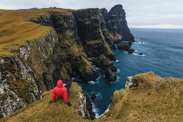 Man enjoying the view of cliffs and sea stack on Suduroy island.
