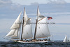 Schooner sails over the ocean waves in the bay near a harbor