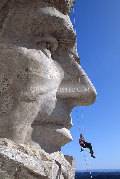 Park Service worker dangles beneath Abe Lincoln carving at Mt. Rushmore during an inspection of the faces. ©Paul Horsted/www.dakotahoto.com.