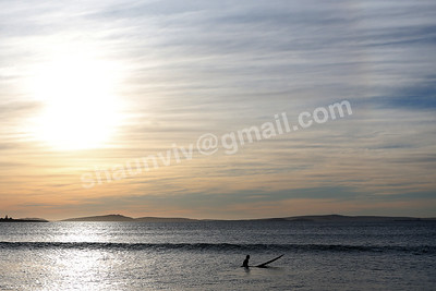 A Surfer waits for waves as the sunsets.