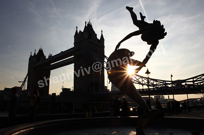Silhouette of Girl with a Dolphin Fountain and Tower Bridge.