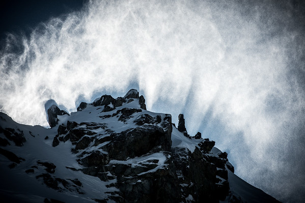 Rays of early morning sun slicing through wind blown snow, Whistler BC