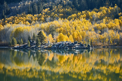 Fall aspens and the old homesite reflecting in the still, morning waters of Marlette Lake.