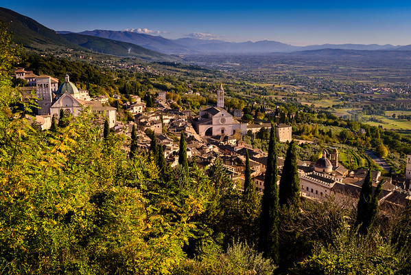 View of Assisi as seen from the road to Rocca Maggiore. On the left is the San Rufino cathedral; in the center is the St. Clare basilica (Basilica di Santa Chiara).