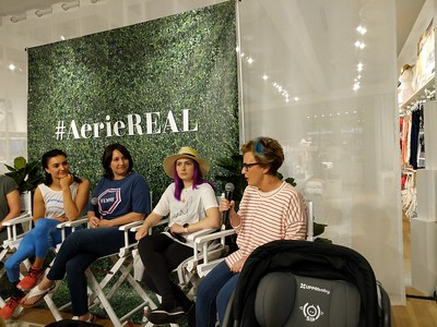 Molly Burke Talk - April 27th, 2019. Aerie Store. Stoneridge Mall. Pleasanton, CA, USA  The people speaking at the event.   Accessibility: A photo of 4 of the 6 speakers at the event. In the background is the Aerie store with the #AerieREAL hashtag with green leaves backdrop.