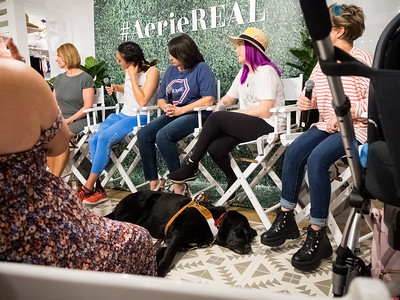 Molly Burke Talk - April 27th, 2019. Aerie Store. Stoneridge Mall. Pleasanton, CA, USA  The people speaking at the event.  Accessibility: A photo of 5 of the 6 speakers at the event. In the background is the Aerie store with part of the #AerieREAL hashtag with green leaves backdrop. In the foreground is Molly Burke's guide dog, Gallop, napping on the ground.