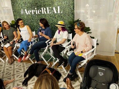 Molly Burke Talk - April 27th, 2019. Aerie Store. Stoneridge Mall. Pleasanton, CA, USA  The people speaking at the event.  Accessibility: A photo of 5 of the 6 speakers at the event. In the background is the Aerie store with the #AerieREAL hashtag with green leaves backdrop. In the foreground is Molly Burke's guide dog, Gallop, napping on the ground.