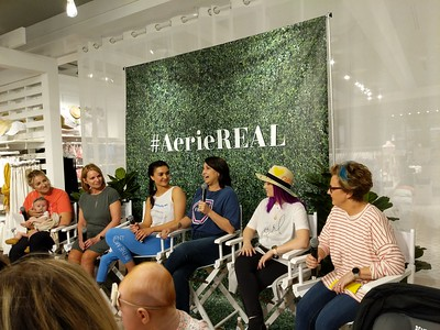 Molly Burke Talk - April 27th, 2019. Aerie Store. Stoneridge Mall. Pleasanton, CA, USA  The people speaking at the event.   Accessibility: A photo of the 6 speakers at the event. In the background is the Aerie store with the #AerieREAL hashtag with green leaves backdrop.