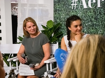 Molly Burke Talk - April 27th, 2019. Aerie Store. Stoneridge Mall. Pleasanton, CA, USA  Another speaker at the event.   Accessibility: A photo of 2 of the 6 speakers at the event. In the background is part of the Aerie store with the #AerieREAL hashtag with green leaves backdrop.