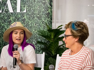Molly Burke Talk - April 27th, 2019. Aerie Store. Stoneridge Mall. Pleasanton, CA, USA  Molly Burke​ and her mom.  Accessibility: A photo of Molly Burke (left) and her mom (right) at the event. In the background is the Aerie store with part of the #AerieREAL hashtag with green leaves backdrop.