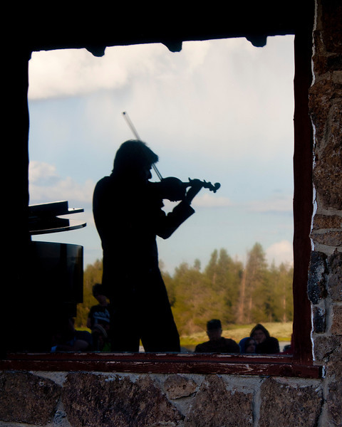 Silhouette of Eric Grossman reflected in the glass while playing a violin concert for the students and friends of the Mountains and Strings retreat at the beautiful Harriman State Park in Island Park, Idaho. July 13, 2011.