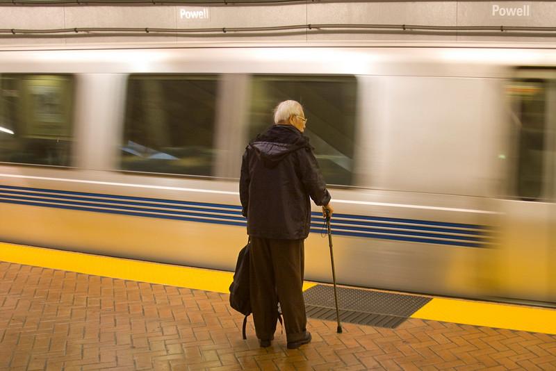 Man waits as train goes by in Powell Street BART station, Nov 2007. San Francisco, California.