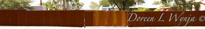 Corrugated rusty metal fencing_5770