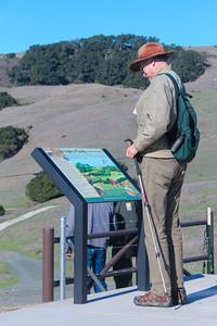 A visitor reads the interpretive signage at La Honda Creek Open Space Preserve.