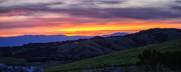 Layers of sunrise glow beyond the mountains.