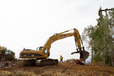 An excavator works in tandem with a crewmember to sort building materials in preparation for recycling.
