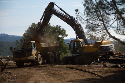 Large six-wheeled articulated dump trucks are used to move building materials around the site.